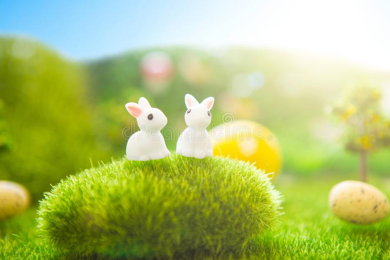 Happy Easter concept. Colorful Easter eggs and rabbits toys on green grass. Fairy tale sunset on the plastic green field with plas royalty free stock photos