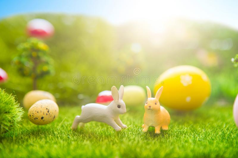 Happy Easter concept. Easter rabbits toy on spring green grass. Fairy tale sunset on the plastic green field with plastic grass, m royalty free stock photography