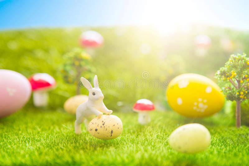 Happy Easter concept. Little Easter bunny toys and Easter eggs on green grass. Fairy tale sunset on the plastic green field with p royalty free stock images