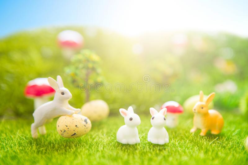 Happy Easter concept. Little Easter bunny toys and Easter eggs on green grass. Fairy tale sunset on the plastic green field with p royalty free stock image