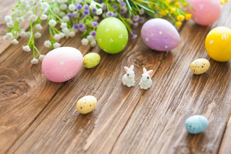 Happy Easter concept. Rabbits with easter eggs on wooden table. Cute Little easter bunny stock photography
