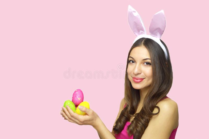 Happy Easter concept. Sweet young woman with bunny ears holding colorful Easter eggs looking at camera over pink background. stock photos