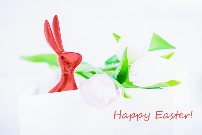 Happy Easter. Easter coral color bunny and delicate tulips on a white background royalty free stock image