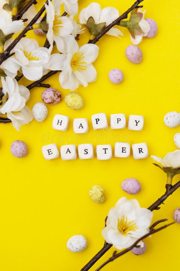 Happy Easter. Cubes with text on yellow background. Spring brunches with white flowers and candy, chocolate easter eggs. Happy Easter. Cubes with text on yellow stock photo