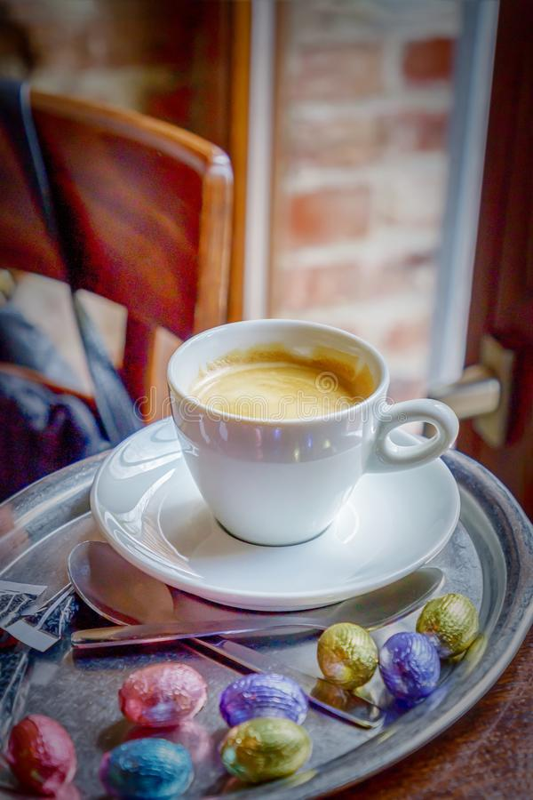 Happy Easter. Cup of coffee espresso and colorful chocolate eggs stock photo
