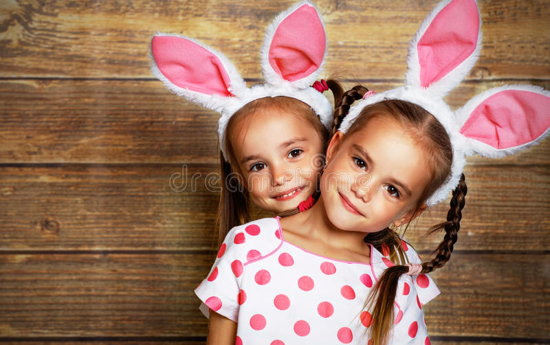 Happy easter! cute twins girls sisters dressed as rabbits on wo. Oden background royalty free stock image