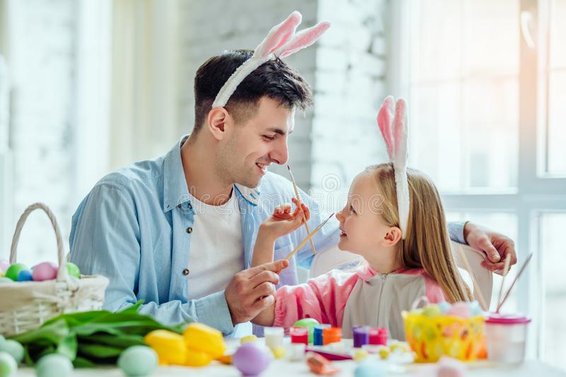 Happy easter!Dad and his little daughter together have fun while preparing for Easter holidays.On the table is a basket with stock images
