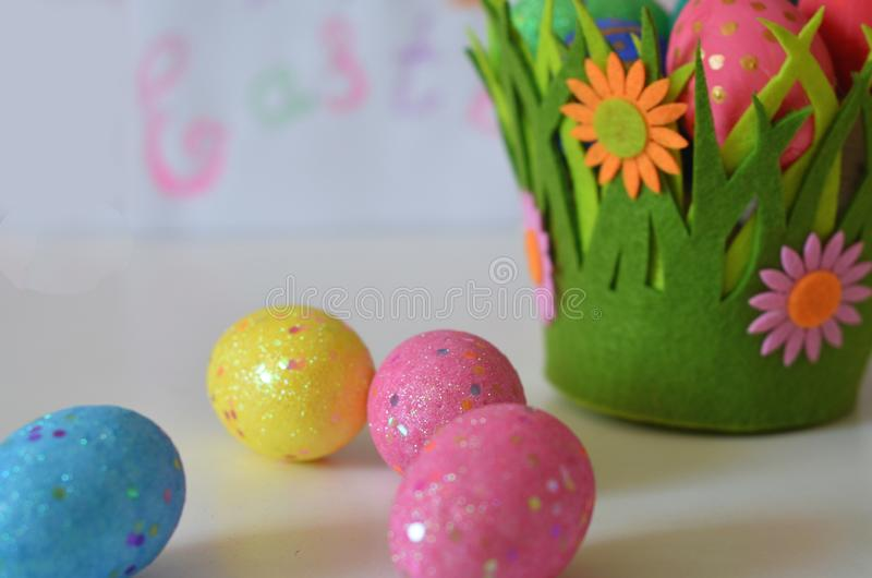 Happy Easter Day. Easter eggs concept. Closeup Colorful Easter eggs in nest and basket green crass on white wooden background royalty free stock images