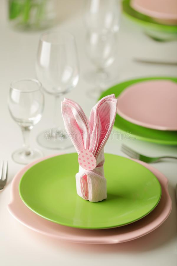 Happy easter. Decor and table setting of the Easter table - Branches of flowering spring tree, dishes of pink and green color stock photos
