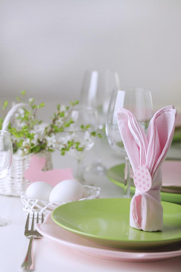 Happy easter. Decor and table setting of the Easter table is a vase with pink tulips and dishes of pink and green color royalty free stock photography