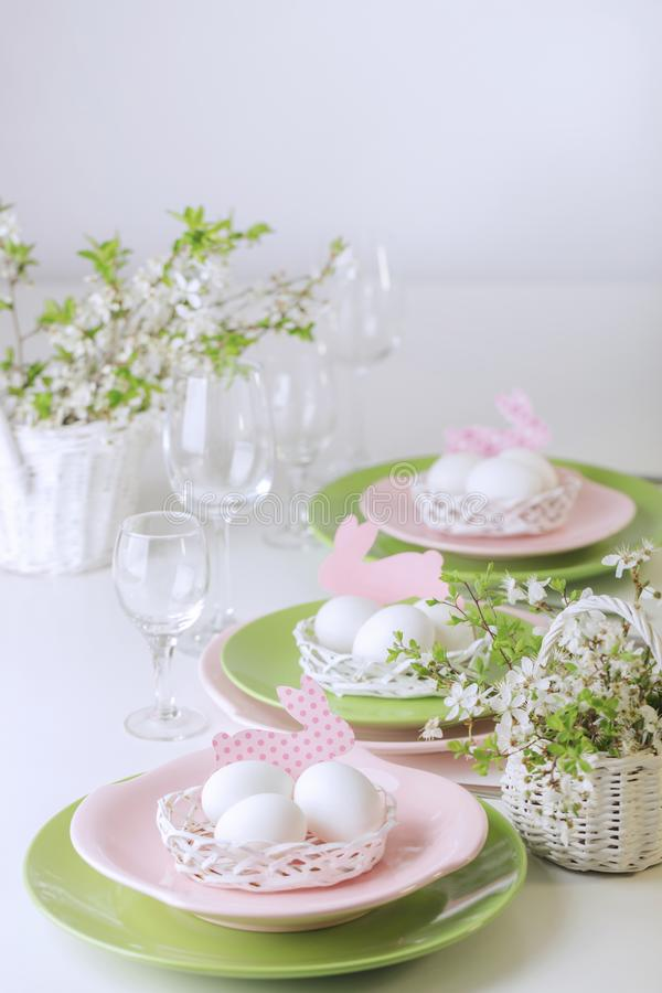 Happy easter. Decor and table setting of the Easter table is a vase with pink tulips and dishes of pink and green color. Selective focus stock photo