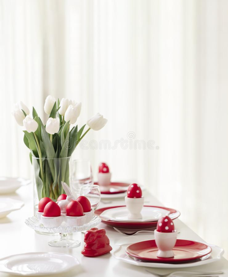 Happy easter. Decor and table setting of the Easter table is a vase with white tulips and dishes of red and white color. Easter. Colored eggs with white polka stock photos