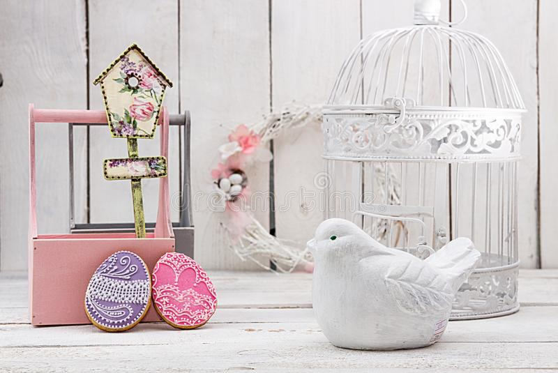 Happy Easter decoration for greeting card. Wooden bird, birdhouse, gingerbread Easter cookies in shape of Easter eggs on white ba stock photography