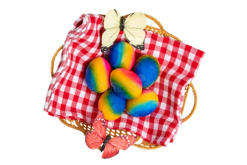 Happy easter decorations background. Top view of colorful easter eggs in a basket on red checkered napkin and two butterflies royalty free stock photos