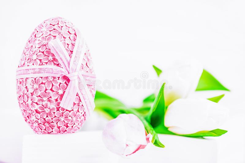 Happy Easter. Easter blue egg and white and pink tulips on a white background stock photos