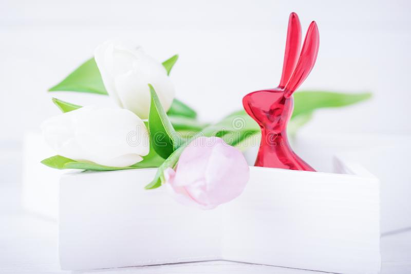 Happy Easter. Easter bunny and delicate tulips on a white background. Copy space royalty free stock photo