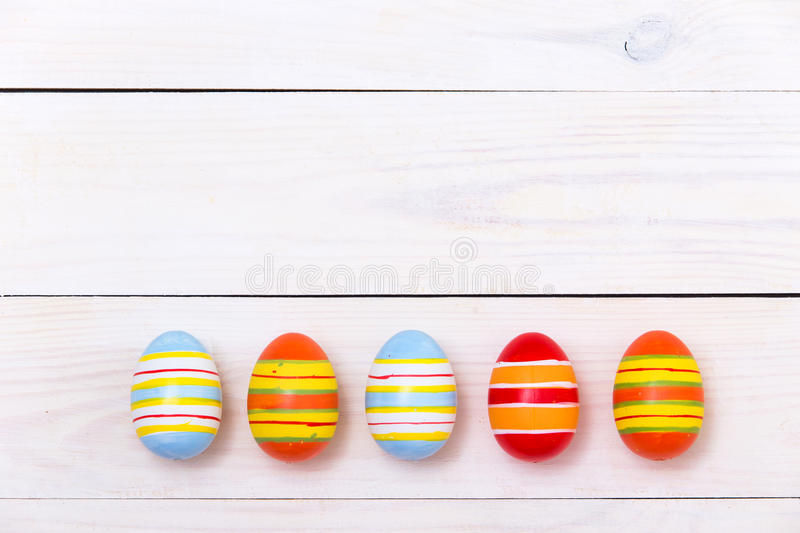 Happy Easter! Easter Colorful eggs on white wooden background. Top view with copy space stock image
