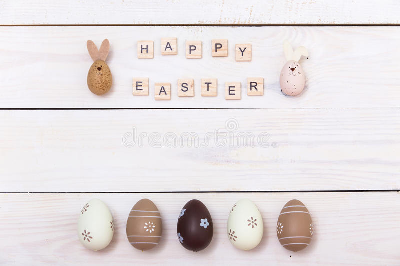 Happy Easter! Easter eggs Painted in pastel colors on white wooden background. Top view with copy space stock photos