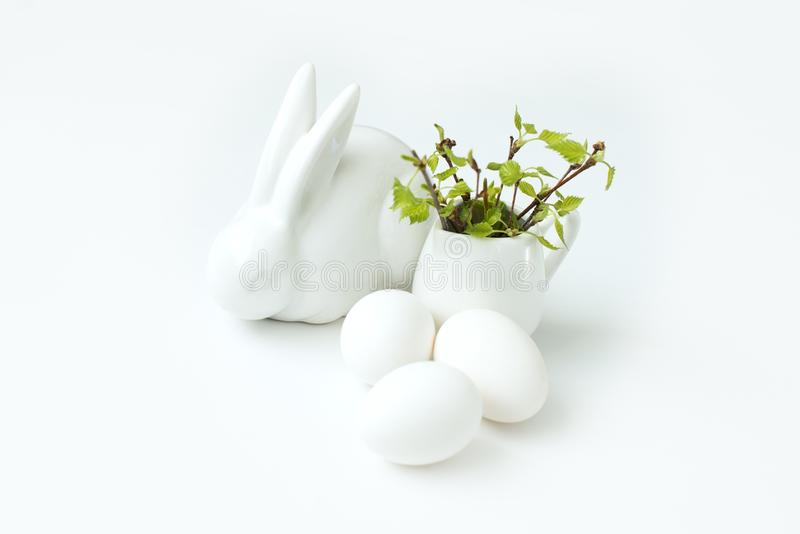 Happy Easter eggs and branch white background and white easter bunny. Happy easter egg and branch with young leaves on white background and white easter bunny stock image
