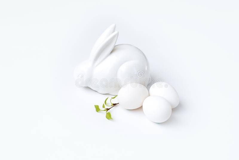Happy Easter eggs and branch white background and white easter bunny. Happy easter egg and branch with young leaves on white background and white easter bunny royalty free stock photo