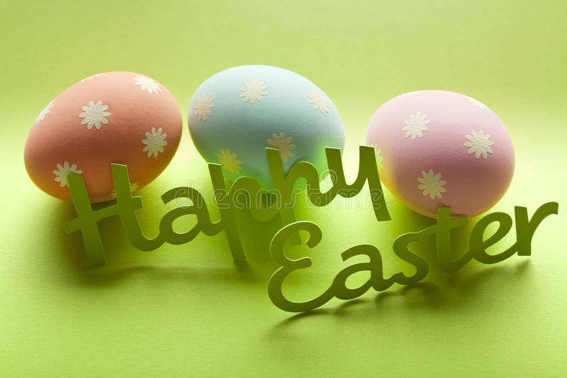 Happy Easter - eggs and inscription on green background royalty free stock photo