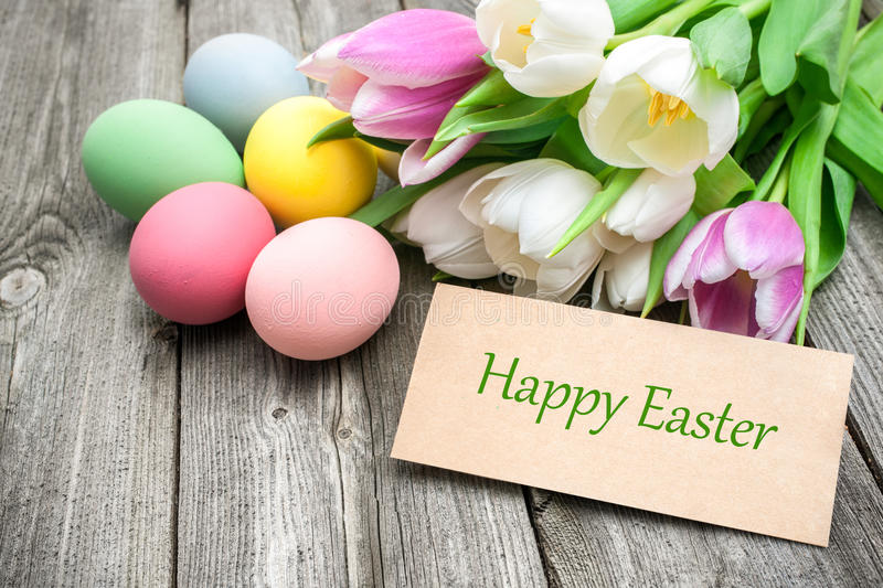 Happy Easter. Easter eggs and tulips with a tag on wooden background
