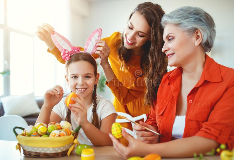 Happy Easter! family grandmother, mother and child paint eggs and prepare for holiday. Happy Easter! family grandmother, mother and child paint eggs and prepare stock photos