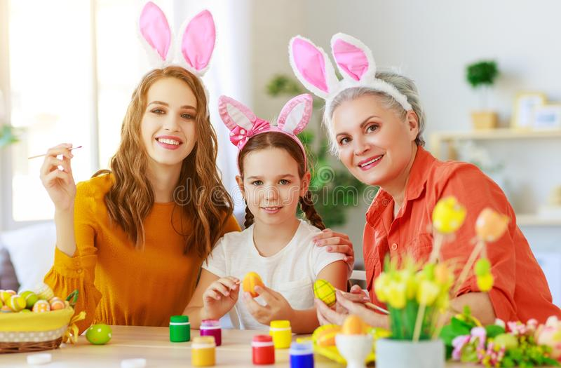 Happy Easter! family grandmother, mother and child paint eggs and prepare for holiday royalty free stock photos