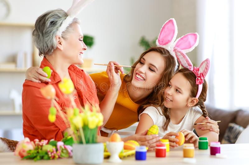 Happy Easter! family grandmother, mother and child paint eggs and prepare for holiday. Happy Easter! family grandmother, mother and child paint eggs and prepare stock photo