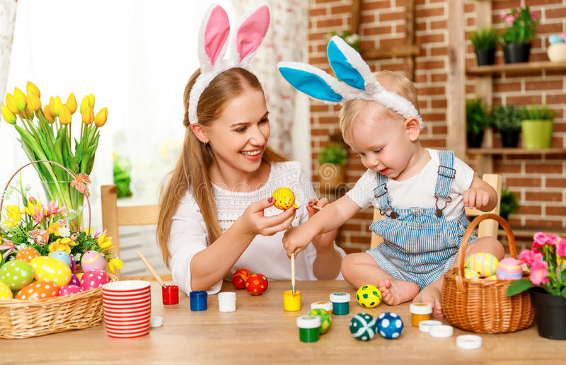 Happy easter! family mother and baby son paint eggs for holiday stock photo