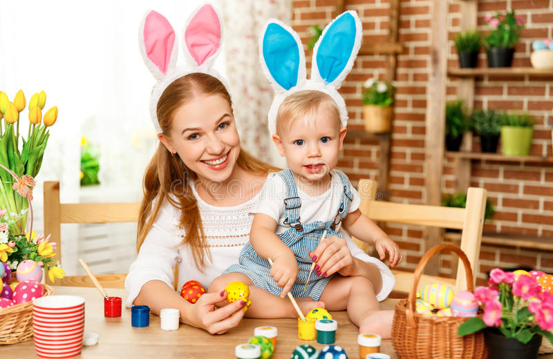 Happy easter! family mother and baby son paint eggs for holiday. Easter at home stock images