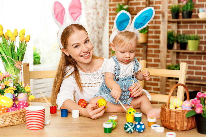 Happy easter! family mother and baby son paint eggs for holiday stock image