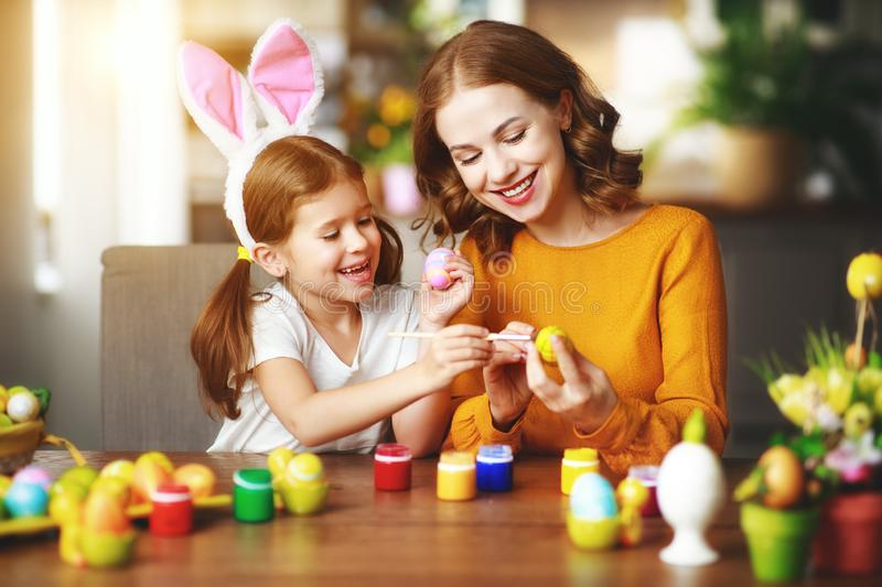 Happy easter! family mother and child daughter with ears hare getting ready for holiday. A Happy easter! family mother and child daughter with ears hare getting stock photo
