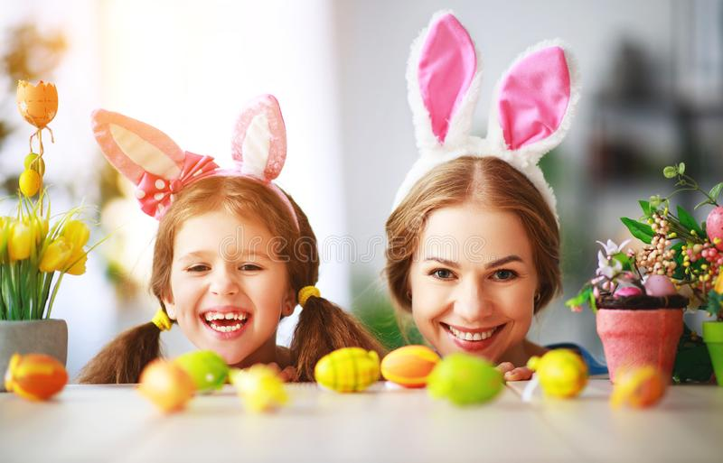 Happy easter! family mother and child daughter with ears hare getting ready for holiday. A Happy easter! family mother and child daughter with ears hare getting royalty free stock photos