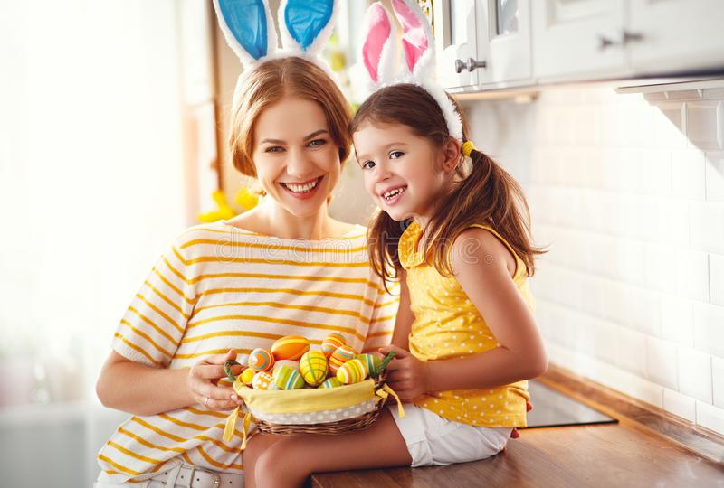 Happy easter! family mother and child daughter with ears hare getting ready for holiday. A Happy easter! family mother and child daughter with ears hare getting royalty free stock photography