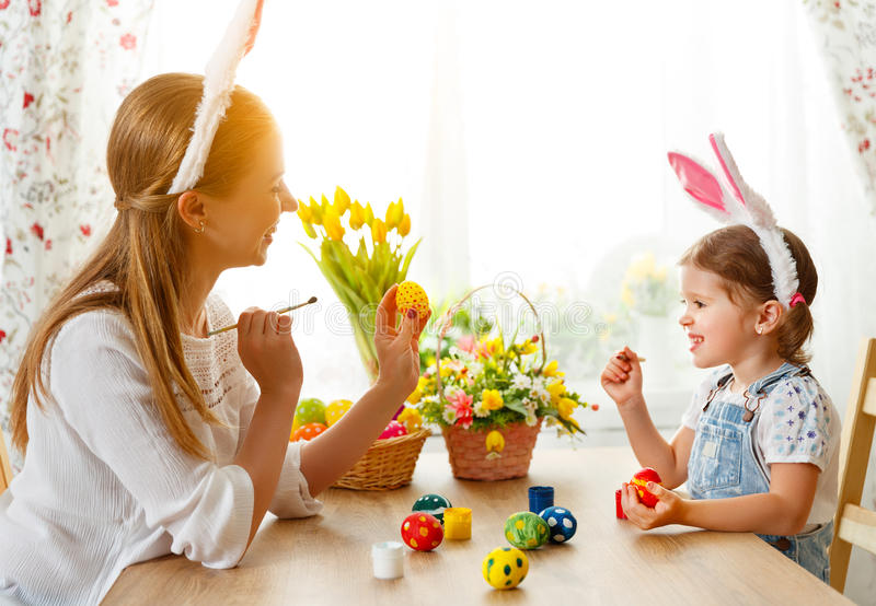 Happy easter! family mother and child daughter paint eggs for ho royalty free stock photos