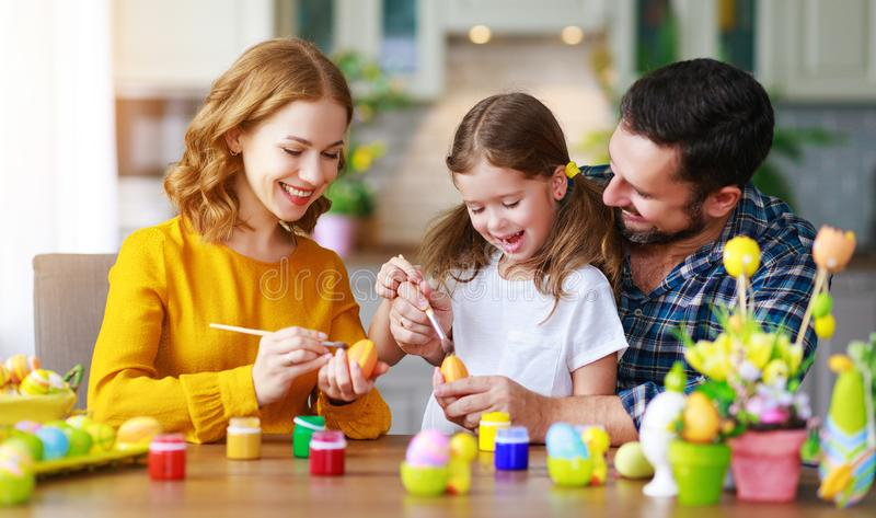Happy easter! family mother, father and child daughter paint eggs for holiday royalty free stock image