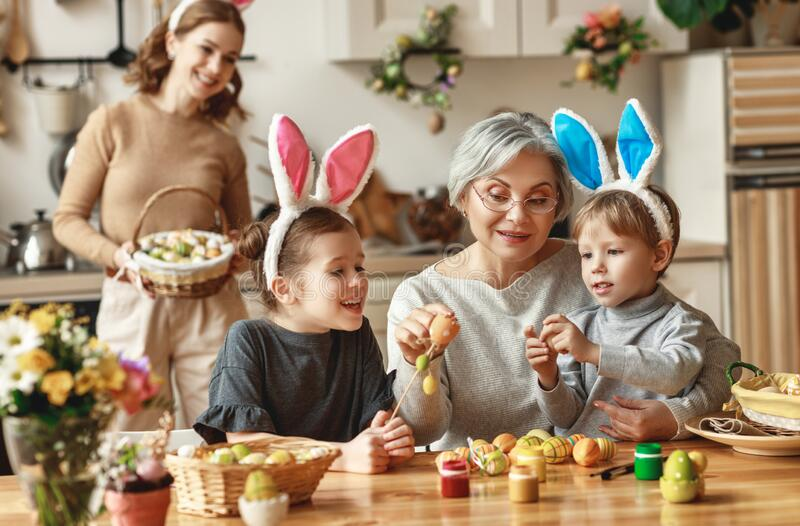 Happy easter! family mother, grandmother and children paint eggs for holiday royalty free stock photography