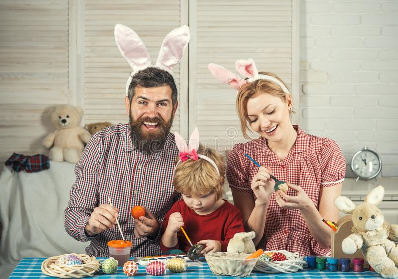 Happy easter family paint eggs. Easter, mother, father and child in bunny ears. Happy family celebrate spring holiday, love. Family values, childhood, art stock photos