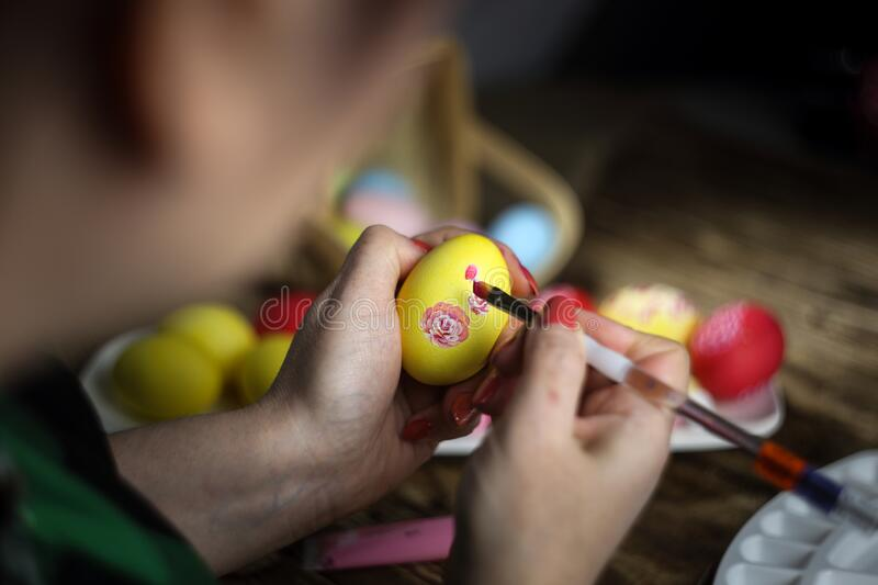 Happy easter! Female hands painting eggs with floral patterns. Preparing for Easter. Artist paints an Easter egg stock photo