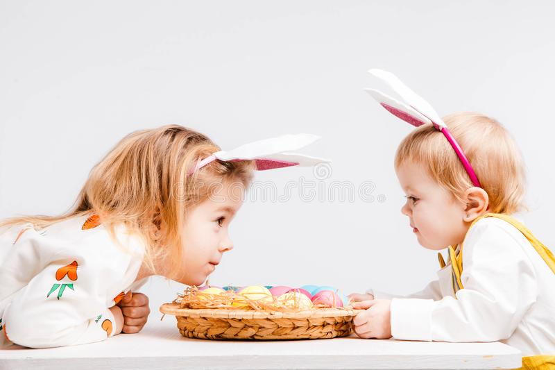 Happy easter. Funny children with rabbit ears celebrate Easter. Light gray background. stock photos