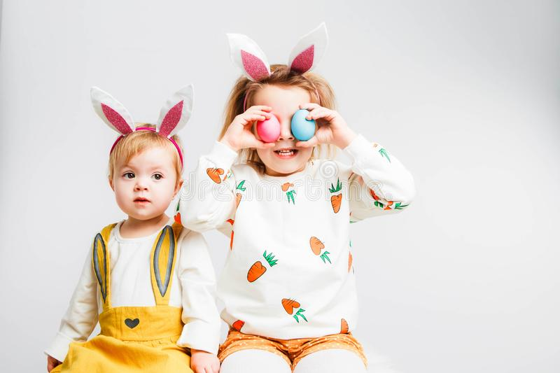 Happy easter. Funny children with rabbit ears celebrate Easter. Light gray background. royalty free stock images