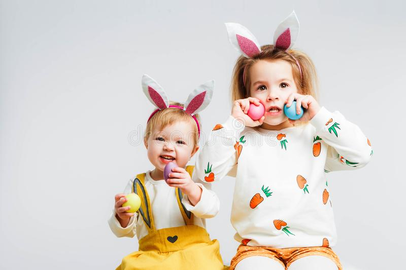 Happy easter. Funny children with rabbit ears celebrate Easter. Light gray background. royalty free stock photos