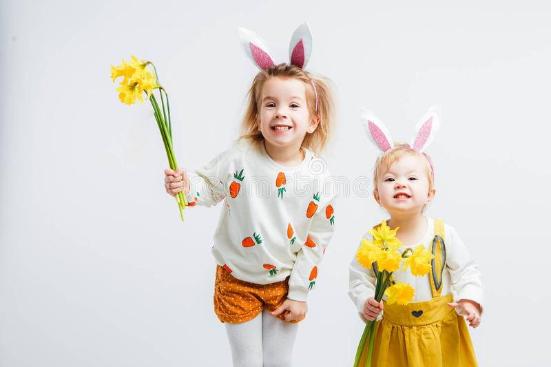 Happy easter. Funny children with rabbit ears celebrate Easter. Light gray background. royalty free stock photo