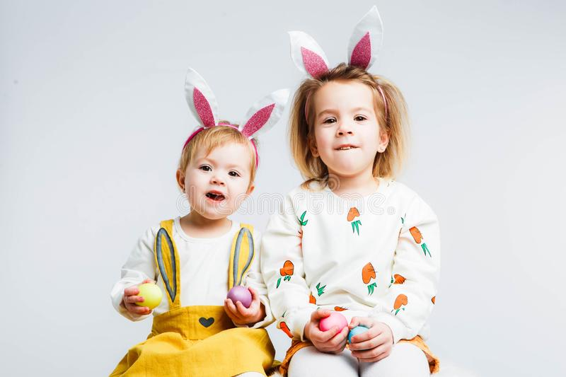 Happy easter. Funny children with rabbit ears celebrate Easter. Light gray background. stock photo