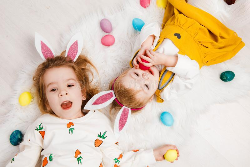 Happy easter. Funny children with rabbit ears celebrate Easter. Light gray background. stock photography