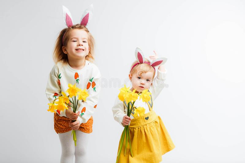 Happy easter. Funny children with rabbit ears celebrate Easter. Light gray background. royalty free stock image