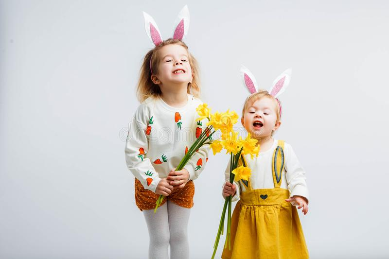 Happy easter. Funny children with rabbit ears celebrate Easter. Light gray background. stock image