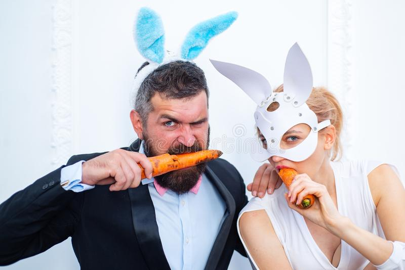 Happy easter and funny easter day. Bunny rabbit ears costume. Surprised bunny couple wearing bunny ears and eat carrot. Happy easter and funny easter day. Bunny royalty free stock photos