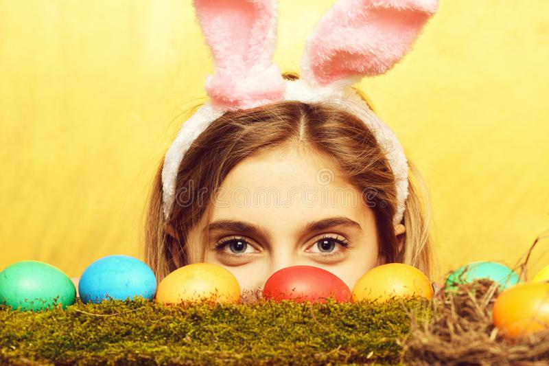 Happy easter girl in bunny ears with colorful eggs, moss. Colorful painted easter eggs on green moss and happy girl in pink bunny ears with cute face on yellow stock photography